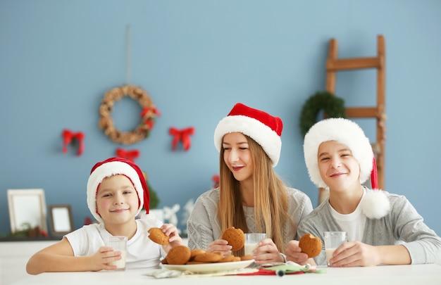 I bambini felici mangiano nella stanza di natale decorata