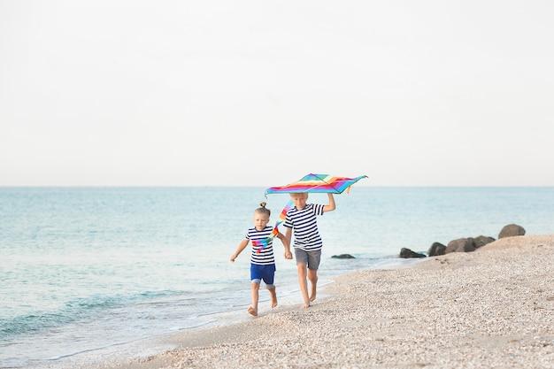 Bambini felici che si divertono in spiaggia. bambini attivi su sfondo estivo.