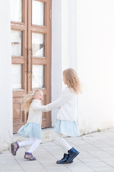 Bambini felici che si tengono per mano due bambine che si godono la vita vortice all'aperto sotto la luce del sole bambino felice