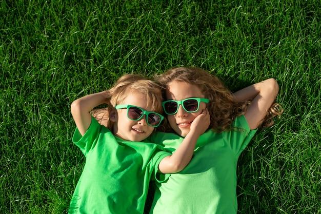 Bambini felici che pongono sull'erba verde. bambini divertenti all'aperto nel giardino di primavera. giornata della terra e concetto di stile di vita sano