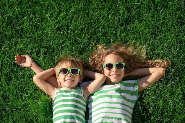 Bambini felici che pongono sull'erba verde. bambini divertenti all'aperto nel giardino di primavera.