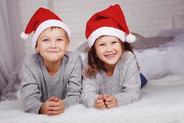 I bambini felici giacciono in berretti di babbo natale
