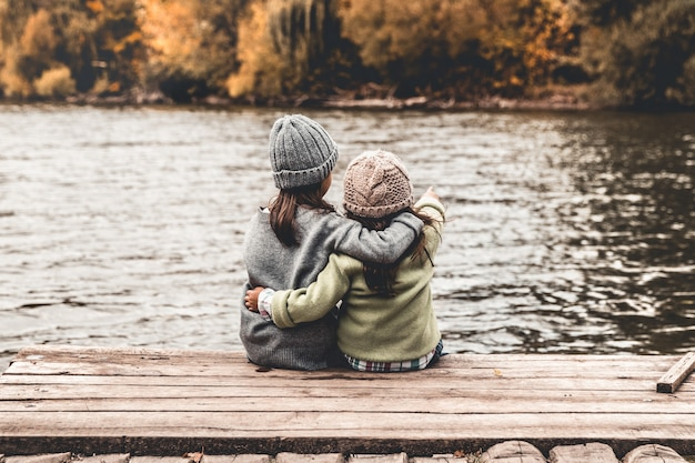 Bambini felici, bambine, sedersi e giocare su un ponte di legno. ritratto. orientamento orizzontale.