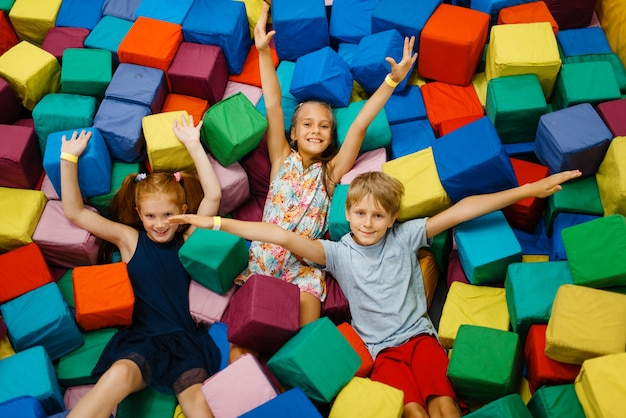 Bambini felici che si trovano in cubi morbidi, parco giochi nel centro di intrattenimento.