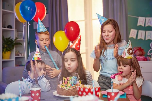 Bambini felici in cappellini per festeggiare un compleanno