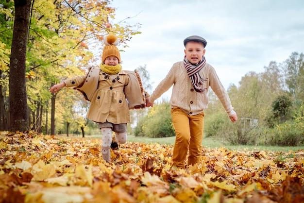Bambini felici che giocano, parco autunnale, calda giornata di sole autunnale. i bambini giocano, foglie d'acero dorate.