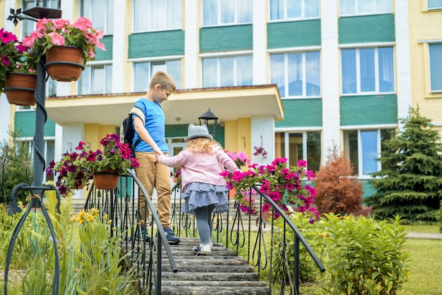 Bambini felici che giocano nel cortile della scuola durante il giorno. passeggiata estiva all'aperto, cortile fiorito, parco verde.