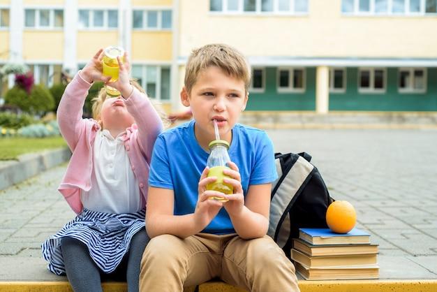 Bambini felici che giocano nel cortile della scuola durante il giorno. colazione scolastica, frutta e succhi. pila di libri di testo, libri. felice e amichevole sorella e fratello