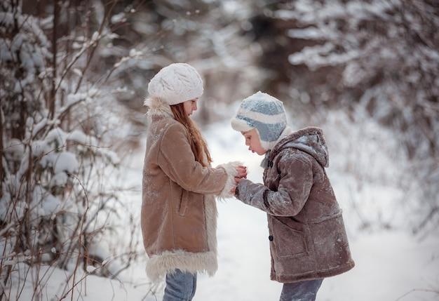 Bambini felici che giocano nella neve in inverno