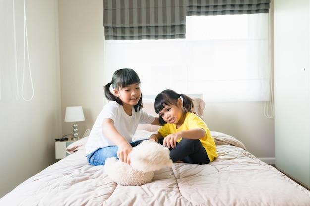 Bambini felici che giocano insieme in camera da letto