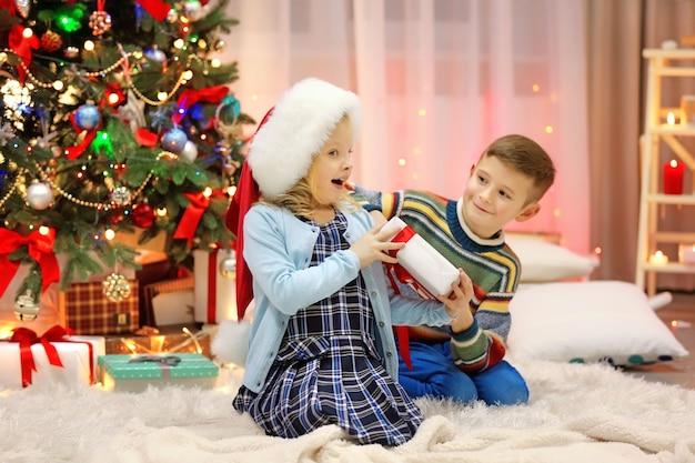 Bambini felici che giocano con i regali nella stanza di natale addobbata