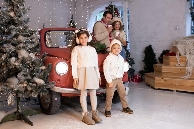 Bambini felici che giocano con la neve vicino all'auto rossa e all'albero di natale, i loro genitori sono vicino a loro. buon natale e buone feste