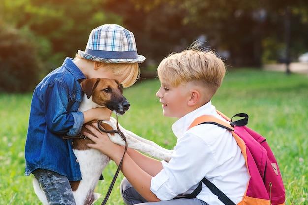 Bambini felici che giocano con il loro cane nel parco