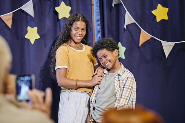 Bambini felici che posano davanti alla telecamera dopo l'esibizione