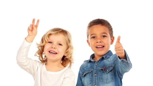Bambini felici che dicono ok e che esaminano macchina fotografica isolata su un bianco