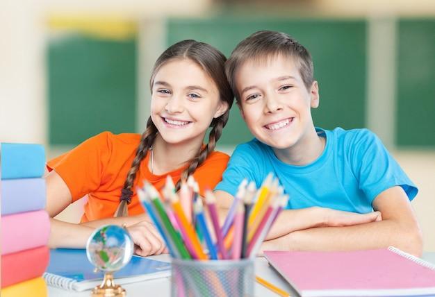Bambini felici seduti a tavola durante la lezione