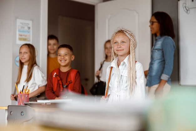 Bambini felici in piedi in classe a scuola