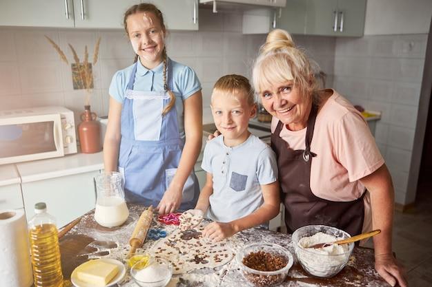 Bambini felici e la loro nonna carina in piedi in cucina