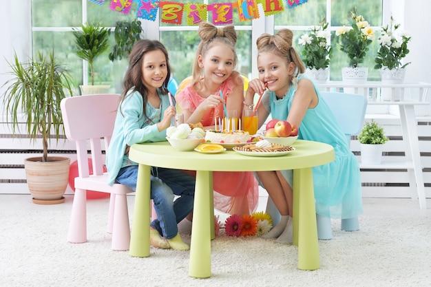 Bambini felici con la torta alla festa di compleanno