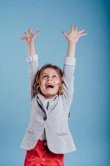 Bambini felici con le mani alzate godendosi la vittoria isolata su uno sfondo blu