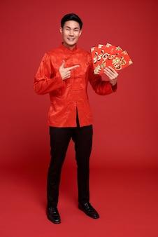 Buon capodanno cinese. uomo asiatico che tiene angpao o regalo monetario pacchetto rosso sul rosso. il testo significa grande fortuna.