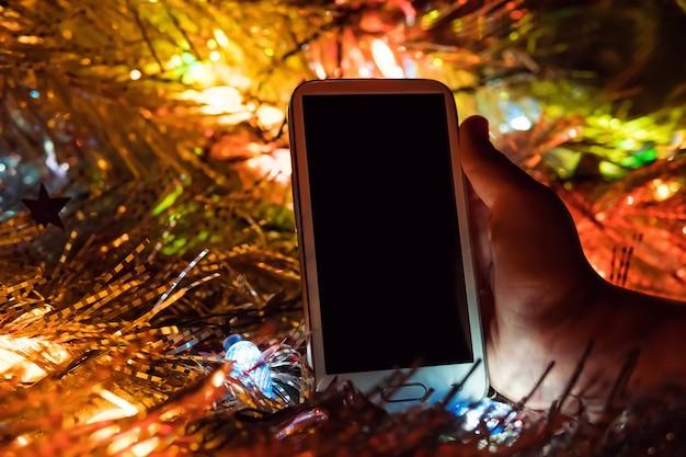 Sfondo di natale felice. la mano che tiene il telefono sullo sfondo delle luci di natale e delle bellissime decorazioni natalizie. regalo di natale alla luce delle luci colorate