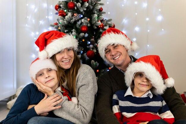 Buon natale in famiglia insieme: mamma papà i bambini si abbracciano e sorridono.