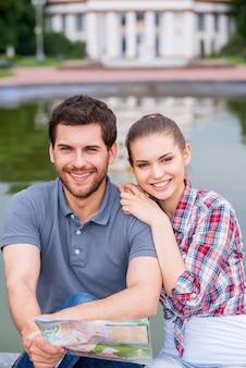 Viaggiatori felici della città. vista dall'alto di una felice coppia di giovani turisti seduti vicino a un bellissimo edificio e guardando la telecamera mentre l'uomo tiene in mano la mappa