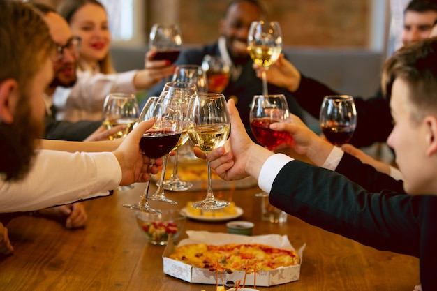 Felici colleghi che festeggiano durante la festa aziendale e l'evento aziendale. giovani caucasici in abiti da lavoro che applaudono, ridono. concetto di cultura dell'ufficio, lavoro di squadra, amicizia, vacanze, fine settimana.