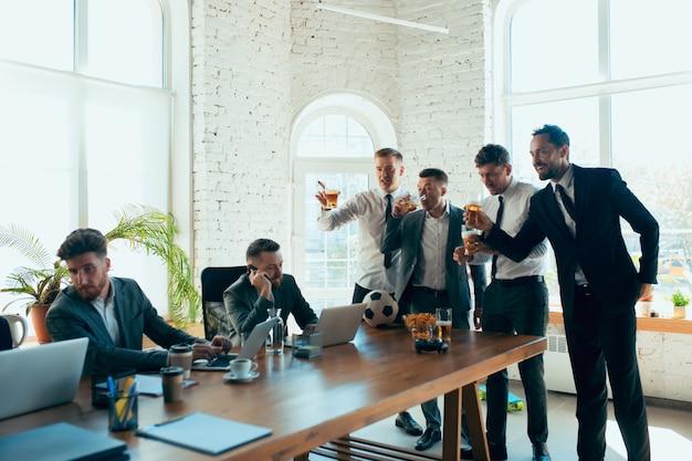 Colleghi felici che si divertono in ufficio mentre i loro colleghi lavorano sodo