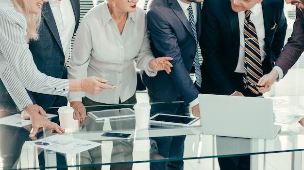 Colleghi felici in piedi vicino alla scrivania in ufficio. concetto di lavoro di successo