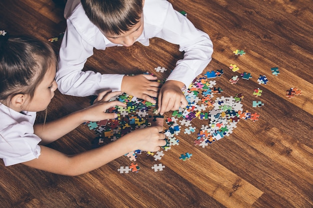 Felice raccogliere puzzle sdraiato sul pavimento del primo piano