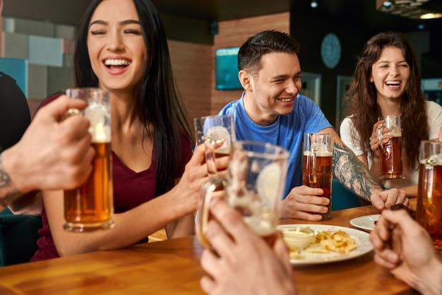 Felice compagnia ridendo e scherzando mentre beve una gustosa birra nel pub. uomini e donne allegri seduti insieme al grande tavolo, mangiando formaggio e salsicce, gustando bevande e riposo concetto di felicità.