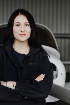 Felice e fiduciosa aviatrice nell'hangar