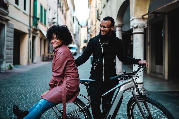 Coppie etniche nere felici e contenti che si siedono sulla bicicletta.