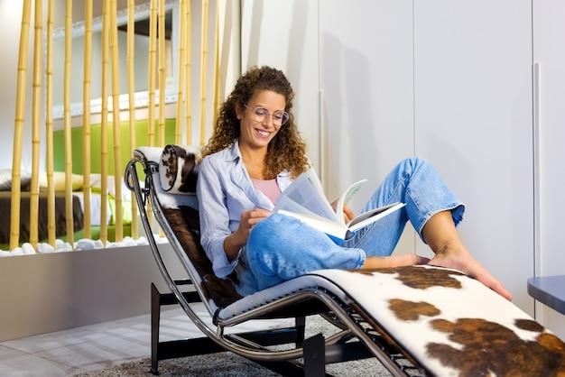 Felice contenta giovane donna con gli occhiali rilassante a piedi nudi su una sedia reclinabile alla moda leggendo un libro con un sorriso