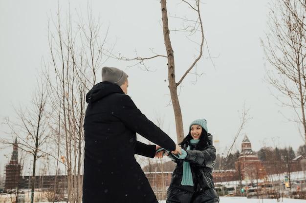 Coppie felici stanno girando nel parco invernale innevato