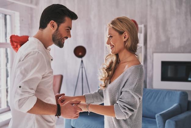 Coppia felice. bella giovane coppia che si tiene per mano e si guarda con un sorriso mentre sta in piedi nella camera da letto