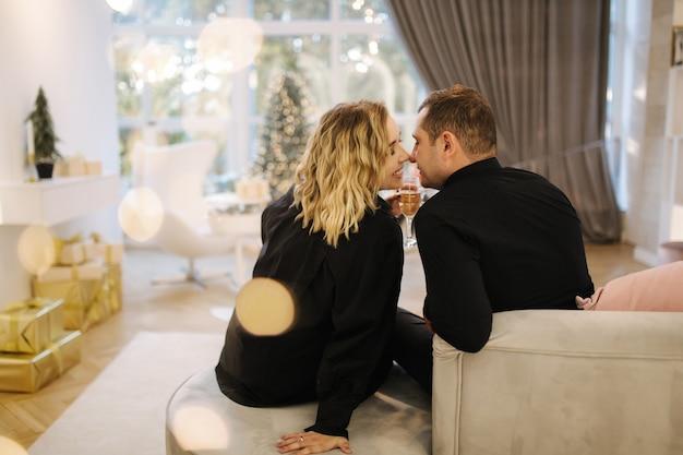 Coppia felice in camicie nere con bicchieri di champegne selebrate il nuovo anno.