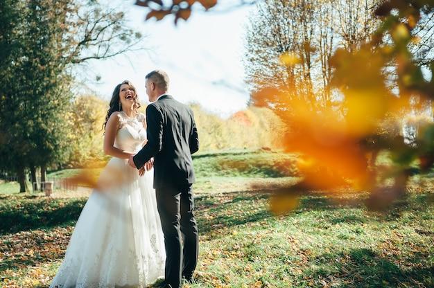 Coppia felice di spose che camminano nella sosta di autunno