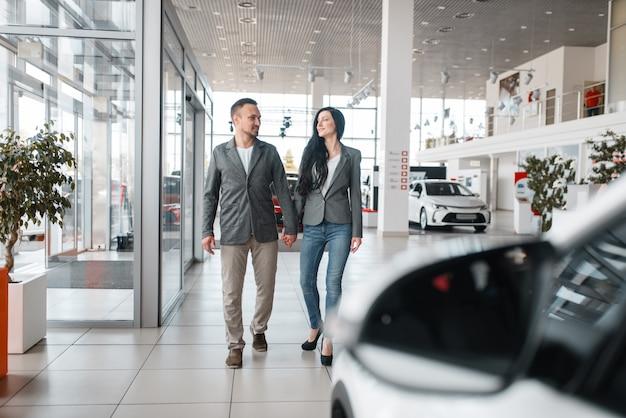 Coppie felici che comprano auto nuove in showroom