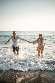 Coppia felice in riva al mare. amanti della luna di miele. uomo e donna sull'isola. bella coppia divertirsi in riva al mare. coppia felice in vacanza. uomo e donna in riva al mare.