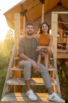 Coppia felice in abbigliamento casual che riposa sulla scala in legno