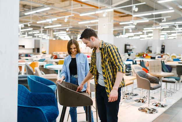 Coppia felice scegliendo bar sedia nello showroom del negozio di mobili.