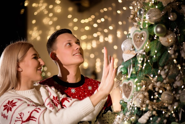 Coppia felice che decora l'albero di natale insieme a casa.