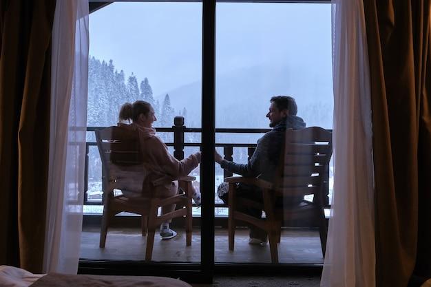 Coppie felici che bevono caffè sul balcone di un hotel di montagna con una bellissima vista sulle montagne