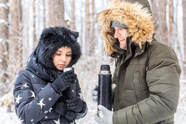 Coppia felice che beve tè caldo nella foresta invernale