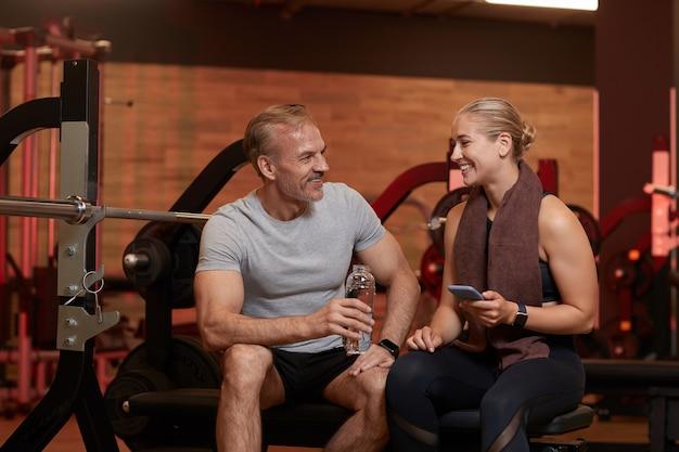 Coppia felice di bere acqua e utilizzare il telefono cellulare e parlare tra loro dopo l'allenamento sportivo in palestra
