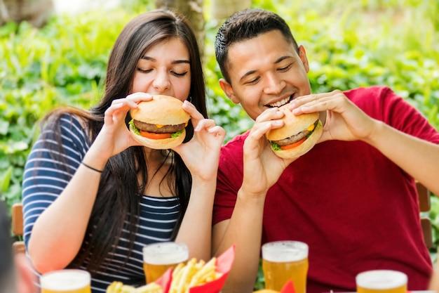 Coppia felice che mangia hamburger e beve birre ghiacciate in un ristorante all'aperto in una vista ravvicinata di loro che sorridono in attesa mentre mordono il cibo