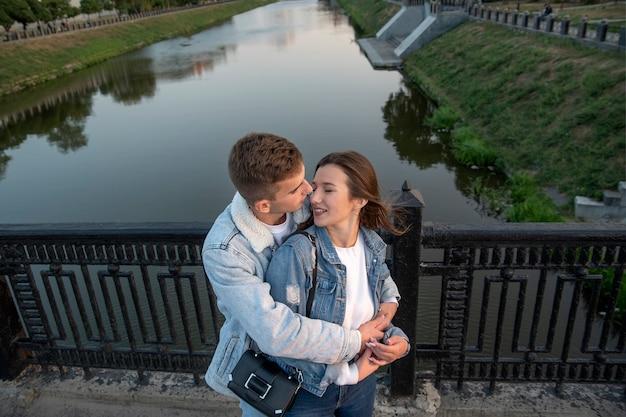 Abbracci di coppia felice sul ponte. guy abbraccia e bacia la sua amata sullo sfondo del fiume. sopra vista. appuntamento romantico.